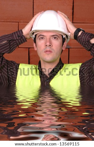 engineer with wait hat with a brick wall as background... - stock photo