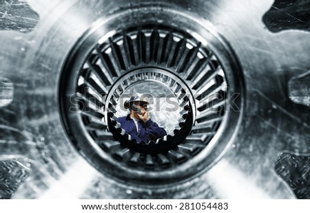 engineer, worker, seen through a large cogwheels axle, focus on the engineer - stock photo