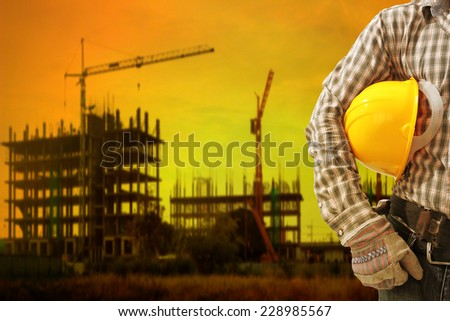 engineer working at high building construction site against beautiful sunset - stock photo