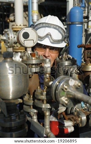 engineer working behind oil and gas pipes inside control-room of refinery - stock photo