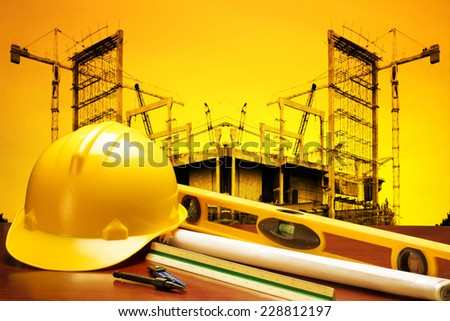 engineer working table plan building model and writing tool equipment and blueprints against building construction crane with beautiful sunset - stock photo