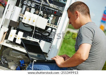 engineer working with laptop outdoors adjusting communication equipment in distribution box - stock photo