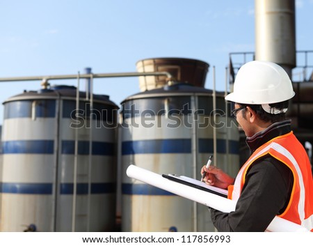engineer  write on notepad with large industry background - stock photo