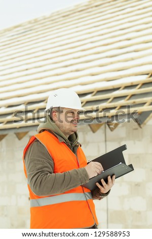 Engineer writing near new building in winter - stock photo