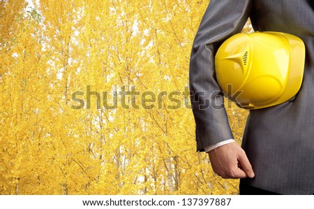 engineer yellow helmet for workers security over yellow autumn forest - stock photo