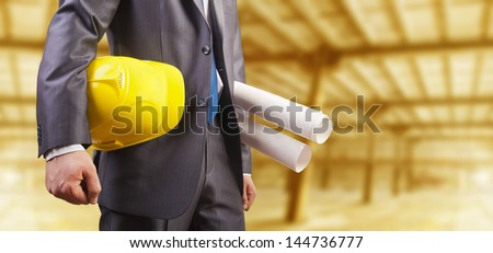 engineer yellow helmet for workers security with construction plans on background empty yellow warenhouse - stock photo