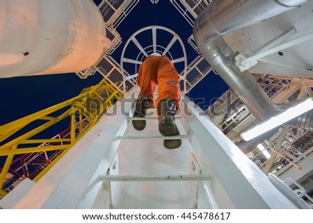 Engineering climb up to oil and gas process plant to observer and inspect gas dehydration processing in night shift  - stock photo