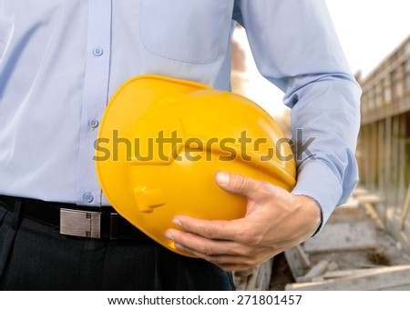 Engineering. Close-up shot of a foreman holding a hardhat on the construction site - stock photo