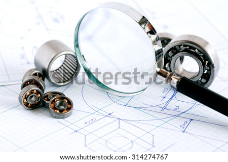 Engineering concept. Closeup of magnifying glass near ball bearings on blueprint with draft - stock photo