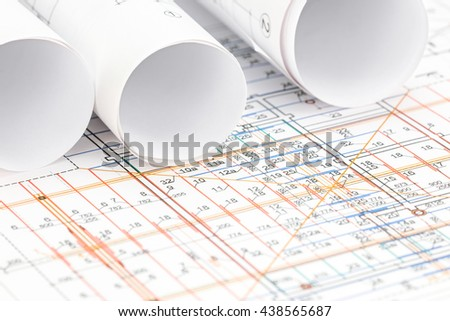 engineering drawing detail and rolls of floor plan blueprints - stock photo