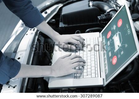 Engineering interface against mechanic using laptop on car - stock photo