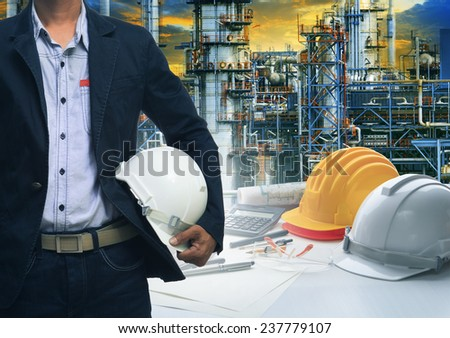 engineering man standing with white safety helmet against  oil refinery in petrochemical industry - stock photo
