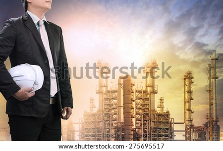 engineering man with safety helmet standing against oil refinery plant in heavy petrochemical industry estate use for fossil energy and petroleum power topic - stock photo