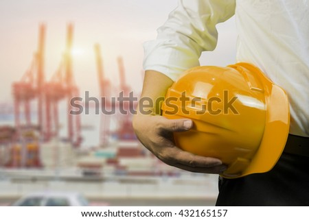 engineering management construction helmet,engineer or worker hold in hand yellow helmet for workers security  on working  site background.  business Man ,management ,selective focus,vintage tone - stock photo