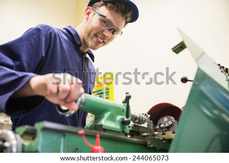 Engineering student using heavy machinery at the university - stock photo