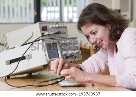 Engineering student using probes for making connections on circuit breadboard for electronics laboratory experiment - stock photo