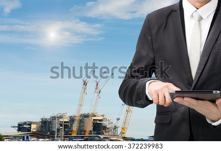 Engineering working hold tablet in front of construction site. - stock photo