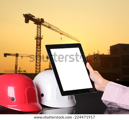 engineering working on computer tablet against beautiful building site  background  - stock photo