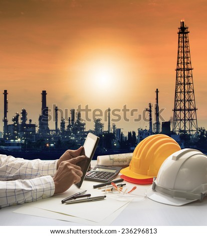 engineering working on computer tablet against silhouette of oil refinery plant in heavy petrochemical industry estate - stock photo