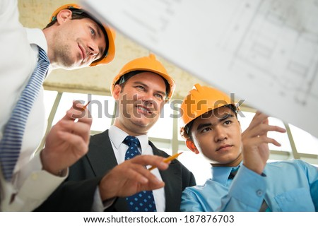 Engineers attentively looking at the plan of the building - stock photo