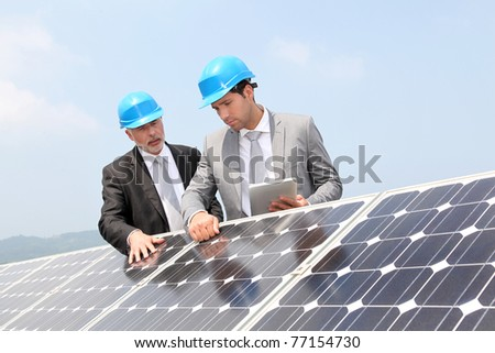 Engineers checking solar panels setup - stock photo