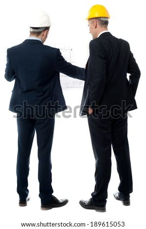 Engineers discuss about project with blueprints - stock photo