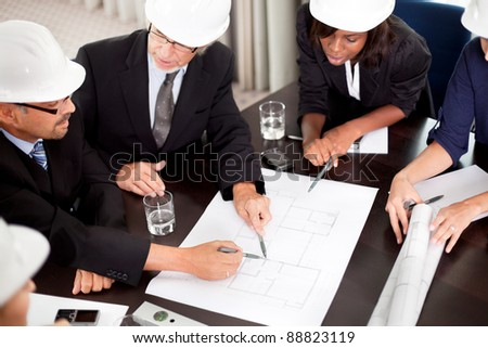 Engineers discussing about a new project around a table pointing at a section on the blueprint. - stock photo