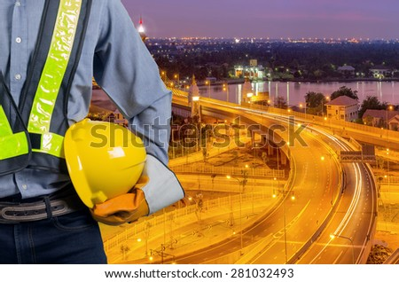 Engineers holding a yellow helmet for the safety of workers with a bridge over the river as a backdrop, During the twilight sky. - stock photo