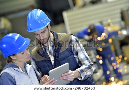 Engineers in steel factory working on digital tablet - stock photo
