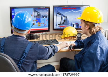 Engineers in the control room, looking at computer monitor.Image of a pump jack at monitor is mine property,mine own work - stock photo