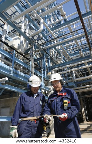 engineers inside oil-refinery with pipelines in background - stock photo