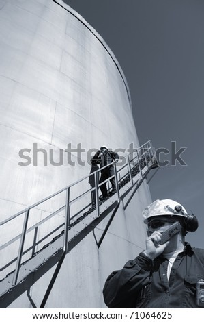 engineers, oil-workers and large fuel-storage tank, inside oil and gas refinery - stock photo