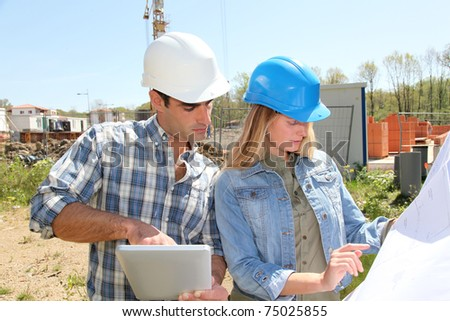 Engineers on construction site with plan - stock photo
