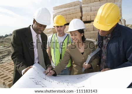 Engineers showing blueprint to workers at construction site - stock photo