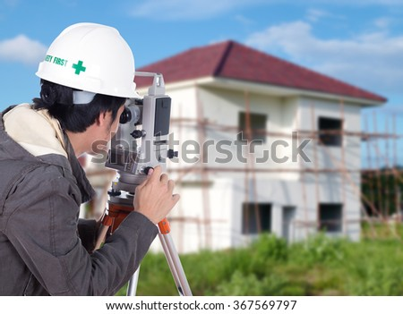 Engineers use tacheometer or theodolite with building construction site background - stock photo