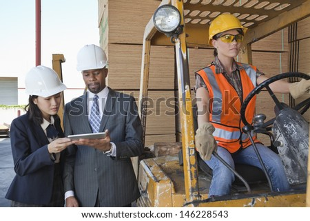 Engineers using tablet PC with female industrial worker driving forklift truck - stock photo