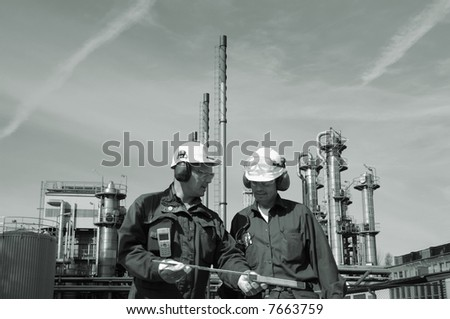 engineers wearing hard-hats in front of oil and gas refinery, background in brownish toning - stock photo