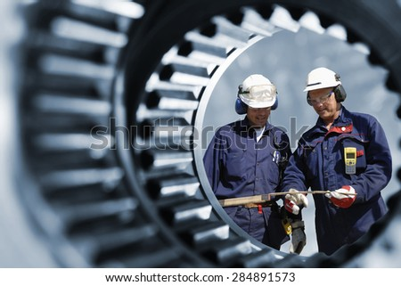 engineers, workers seen through a giant cogwheel and gear axle - stock photo