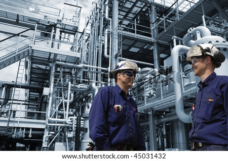 engineers working in chemical-plant, blue toned background - stock photo