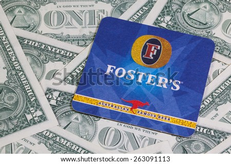 England, London - November 11, 2014:Beermat from Foster's beer and US dollars.Foster's Lager is an internationally distributed Australian brand of lager. - stock photo