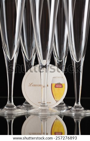 England,London - November 11, 2014:Beermat from Stella Artois and five glasses.It has been brewed in Leuven, Belgium, since 1926.Stella Artois is one of the prominent brands of Anheuser-Busch InBev - stock photo
