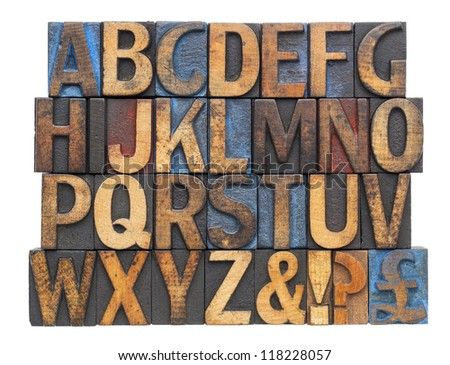 English alphabet with punctuation symbols  in vintage letterpress wood type blocks stained by blue, red and black ink, isolated on white - stock photo