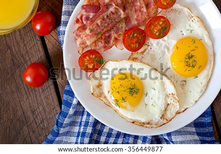 English breakfast -  egg, bacon and vegetables in a rustic style on wooden background. Top view. - stock photo