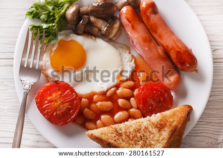 English breakfast: eggs, sausage, tomato, beans and mushrooms close-up on a plate. horizontal view from above  - stock photo
