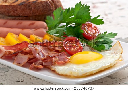 English breakfast - fried eggs, bacon, sausages and toasted rye bread - stock photo