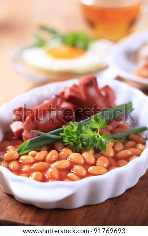 English breakfast of baked beans, sausages, fried egg and bacon  - stock photo