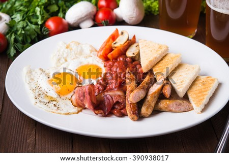 English breakfast (poached eggs, beans, roasted bacon, sausages and vegetables) close up. - stock photo