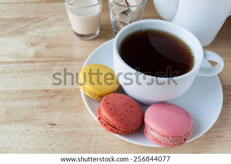 English breakfast tea and macarons on wood  deck - stock photo