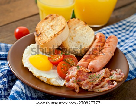 English breakfast - toast, egg, bacon and vegetables in a rustic style on wooden background - stock photo