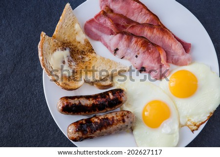 English breakfast with bacon, pork and apple sausages, toast and two fried eggs - stock photo